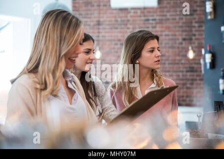 Trois amies, debout au comptoir de cafe Banque D'Images