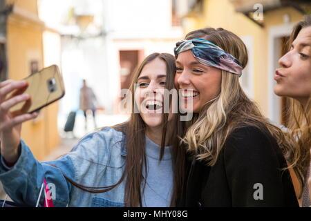 Les amis de prendre la rue en selfies Banque D'Images