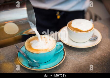 Barista pouring du lait moussé en tasse à café, close-up Banque D'Images