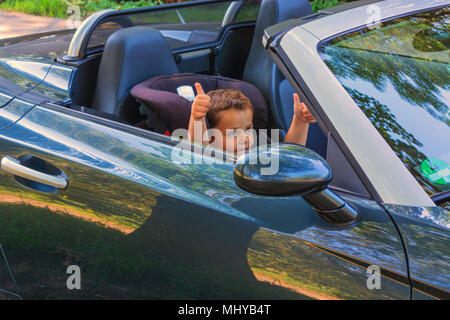 Rire heureux enfant dans un siège convertible dans la voiture un siège pour enfant et montre les pouces vers le haut. Banque D'Images