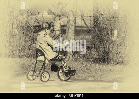 Petite fille sur un vélo rétro à trois roues. Photos jaunies en style retro Banque D'Images