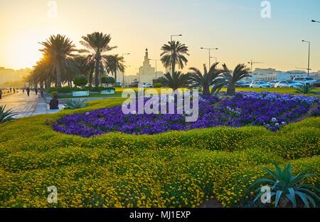 Profitez du beau lever de Seaside Park de Doha avec une vue sur la mosquée derrière la spirale Fanar parterres colorés et palm alley, au Qatar.