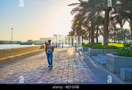 DOHA, QATAR - février 13, 2018: le matin en corniche promenade avec vue sur quelques personnes et bateaux dhow Harbour à Doha, le 13 février à Doha