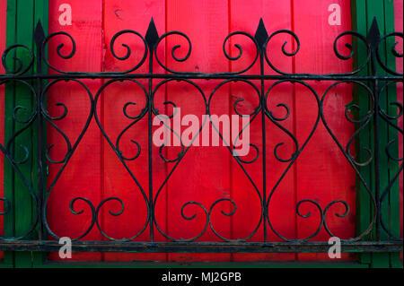 Clôture métallique orné le long du mur rouge Banque D'Images