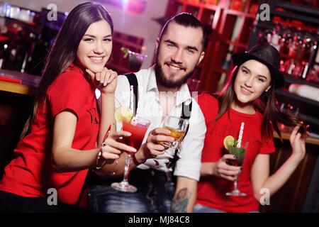 Trois amis - cute guy et deux jeunes filles à un party holding cocktails devant un bar smiling Banque D'Images