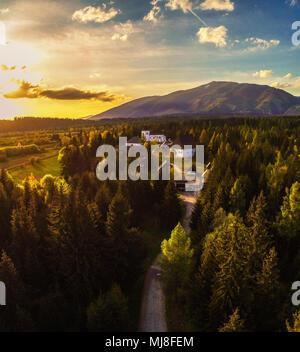 Coucher du soleil au-dessus d'un petit village situé dans la région de hautes montagnes Tatras Banque D'Images