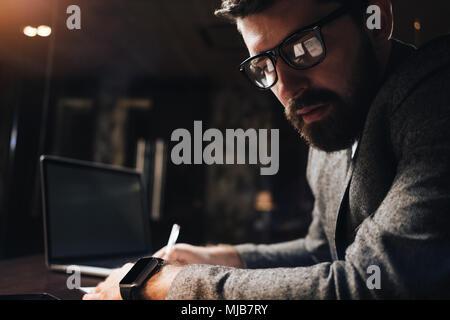 Close-up portrait of businessman barbu dans les verres de nuit bureau loft. Responsable de la création de travailler tard le soir sur un nouveau démarrage en studio coworking Banque D'Images
