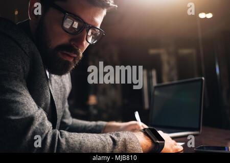 Close-up portrait d'homme barbu portant des lunettes et de nuit smartwatch loft coworking space. Gestionnaire de jeunes créateurs à la route. Nous Man Banque D'Images