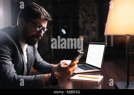 Jeune homme barbu assis par téléphone à l'aide de la table en bois dans un bureau moderne dans la nuit. Les gens qui travaillent les appareils mobiles. Concept de coworking Banque D'Images