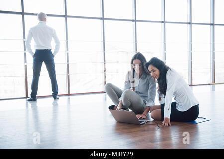 Les jeunes gens créatifs dans un bureau moderne. Groupe de jeunes gens d'affaires travaillent de concert avec l'ordinateur portable. Les pigistes assis sur le plancher. La coopération Banque D'Images