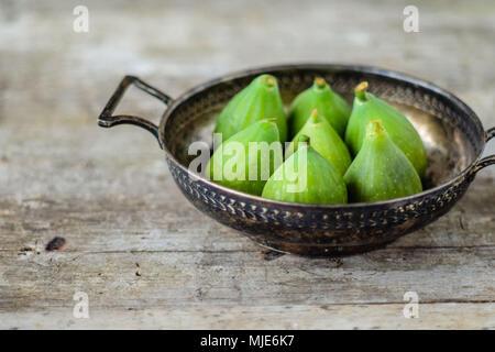 Figues fraîches dans un vieux bol en métal sur une vieille table en bois Banque D'Images