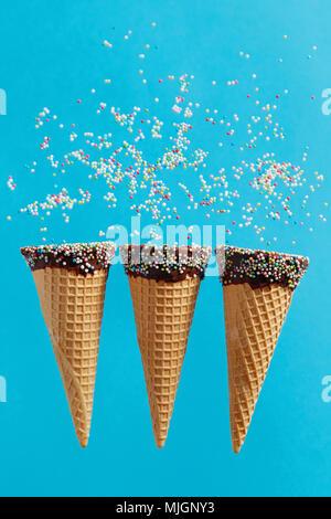 Ice cream cones avec sprinkles multicolores sur fond bleu. Banque D'Images