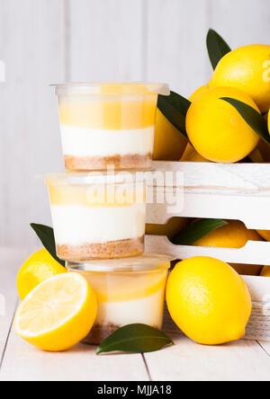 Tasse en plastique à la crème de citron et biscuit dessert avec des citrons en boîte en bois blanc Banque D'Images