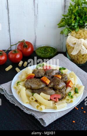 Des pâtes et de foie d'oie poêlé (poulet, canard) avec le pesto et tomates. Banque D'Images