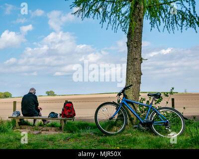 Winton Estate, East Lothian, Ecosse, Royaume-Uni, 6 mai 2018. Laisser les cyclistes de vélos s'appuyant sur les arbres, tandis qu'un homme plus âgé est assis sur un banc de la cycliste et jouit de la vue sur la campagne à travers un champ labouré Banque D'Images
