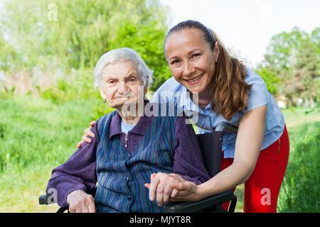 Hauts femme non valide passer du temps avec une jeune personne Banque D'Images