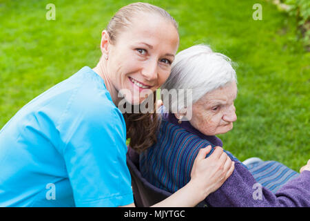 Smiling young carer passer du temps avec une femme handicapée Banque D'Images