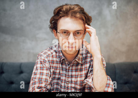 Portrait of handsome et détendue l'homme assis à un café et de penser, travailler, à distance à la recherche sur l'appareil photo Banque D'Images