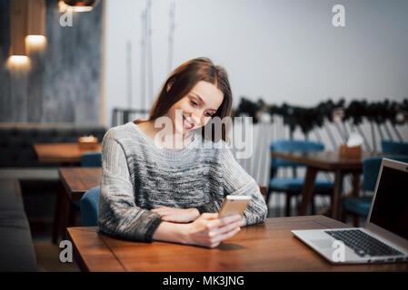 Une jolie fille avec de longs cheveux noirs s'interroge sur un nouveau projet durant une pause-café assis à une table dans un café Banque D'Images