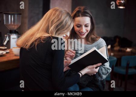 Deux jeunes femmes assises au café à boire du café et profiter de bons livres. Les étudiants sur la pause-café. L'éducation, concept de vie Banque D'Images