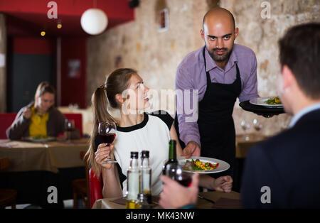 Poli garçon portant des plats commandés à young couple at restaurant Banque D'Images