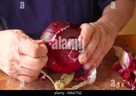 Un homme l'épluchage de la peau externe rugueux d'un gros oignon rouge Banque D'Images