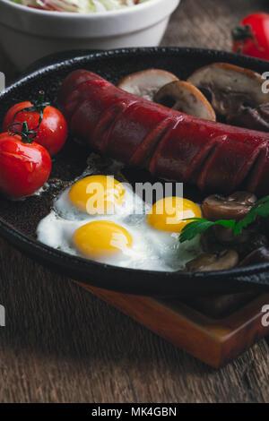 Oeufs de caille au plat, saucisses, tomates et champignons sur le poêle en fonte, petit déjeuner anglais style rustique Banque D'Images
