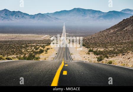 Classic vue panoramique de une interminable route droite qui traverse les paysages arides de la sud-ouest américain Banque D'Images
