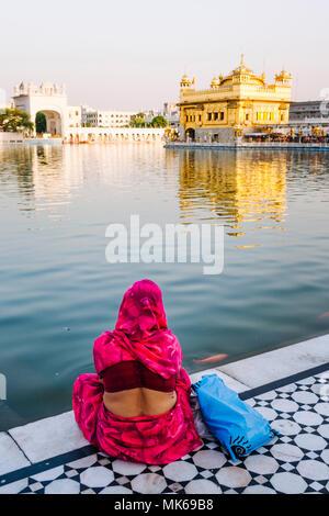 Amritsar, Punjab, India: une femme indienne se trouve par l'Amrit Sarovar extérieure à la recherche au Golden Temple. Banque D'Images