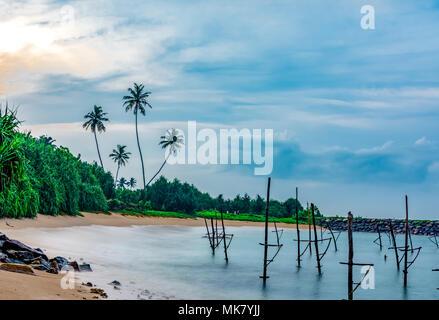 Matin, pêche sur la plage photo avec des cocotiers et des bâtons de pêche en arrière-plan Sri Lankan South Beach destination de voyage Galle