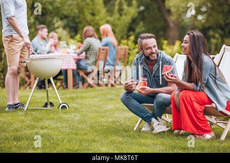 Smiling woman eating watermelon et son ami boire un cocktail dans le jardin pendant une partie Banque D'Images