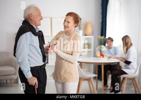 L'attention du personnel médical de l'appel d'offres vers un homme âgé et une femme, parler, expliquer, réconfortant en établissement de soins de luxe chambre commune Banque D'Images