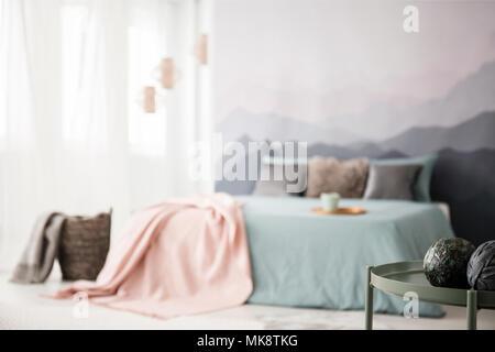 Boules décoratives sur le tableau vert dans une chambre confortable avec intérieur couverture rose on bed