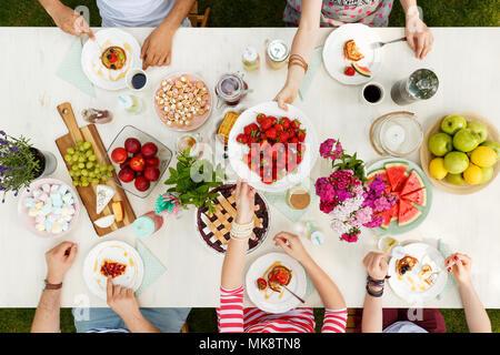 Groupe multiculturel d'un repas, le partage de la nourriture dans le jardin à l'extérieur par une journée ensoleillée Banque D'Images