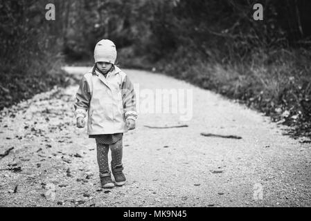 Jeune fille triste enfant est de marcher seul sur les routes de campagne. Triste petite fille est abandonnée dans la nature et à la marche vers le bas. Concept de la solitude, l'abandonner Banque D'Images