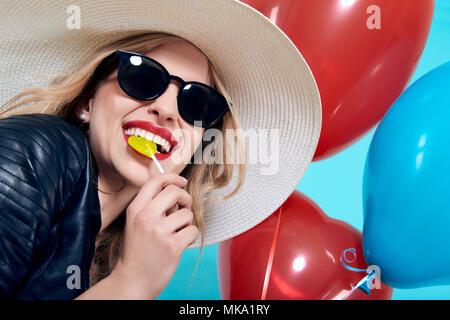 Belle fille à bascule en blouson de cuir et lunettes de soleil en forme de coeur avec lolipop et forme du cœur des ballons. Jolie jeune femme cool fashion portra Banque D'Images