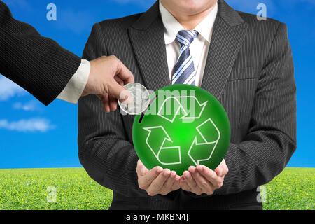 Hands holding coin insérer dans boule verte avec des symboles de recyclage sur fond d'herbe et de ciel bleu. Banque D'Images