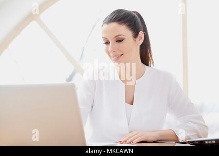 Belle jeune femme à l'aide d'ordinateur portable tout en travaillant en ligne. Bureau à domicile. Banque D'Images