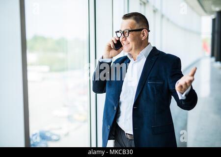 Homme de confiance positif en costume officiel debout à la fenêtre et contempler la ville tout en parlant sur téléphone mobile sur Office Banque D'Images