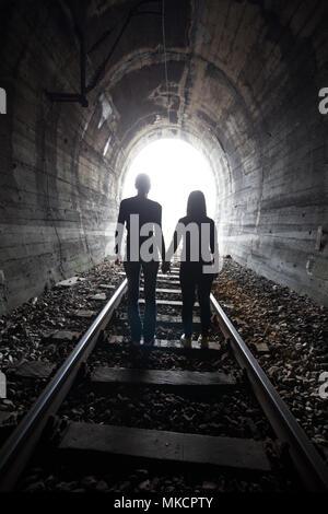 Couple marche main dans la main le long de la voie par un tunnel ferroviaire en direction de la lumière vive à l'autre extrémité, ils apparaissent comme des silhouettes contre le Banque D'Images