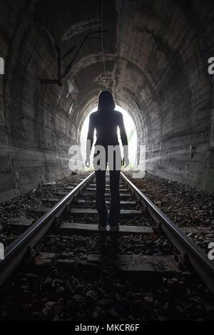 L'homme qui se profile dans un tunnel debout au milieu de la voie ferrée à la recherche vers la lumière au bout du tunnel dans une image conceptuelle Banque D'Images