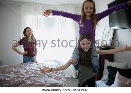 Playful girl Portrait soeur portant sur les épaules dans la chambre Banque D'Images