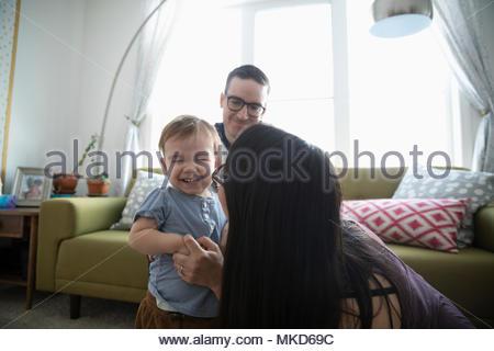 Les parents affectueux jouant avec laughing baby son in living room Banque D'Images