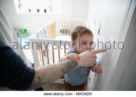 Curieux fils père regarder pousser l'interrupteur d'éclairage en pépinière Banque D'Images