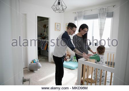 Les parents affectueux avec bébé fils lors de huche de pépinière Banque D'Images