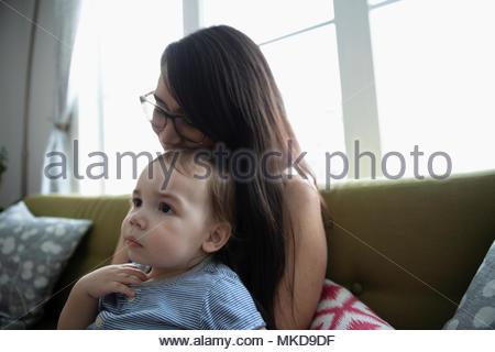 Affectueux, tendre mother holding baby son sur canapé Banque D'Images
