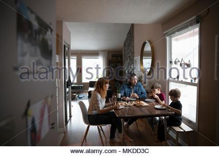Family eating pizza à table à manger Banque D'Images