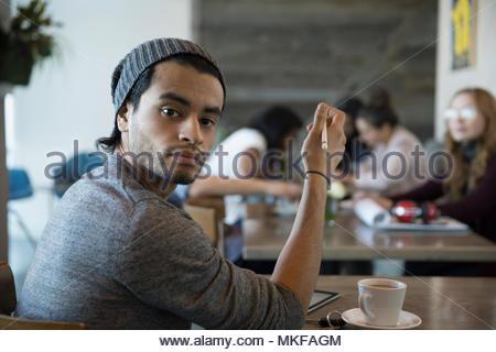 Confiant, Portrait jeune homme créatif avec stylet using digital tablet in cafe Banque D'Images