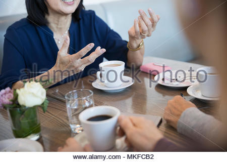 Senior woman de communiquer avec des amis, faisant des gestes avec les mains en cafe Banque D'Images