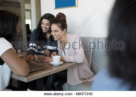 Souriante jeune femme amis parler, boire du café et à l'aide de smart phone in cafe Banque D'Images